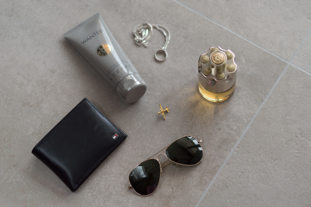 Nicolas's new essentials include: aviator Ray-Ban sunglasses, a Tommy Hifiger wallet, a ring pendant necklace and the shower gel + Eau de toilette Wanted by Azzaro