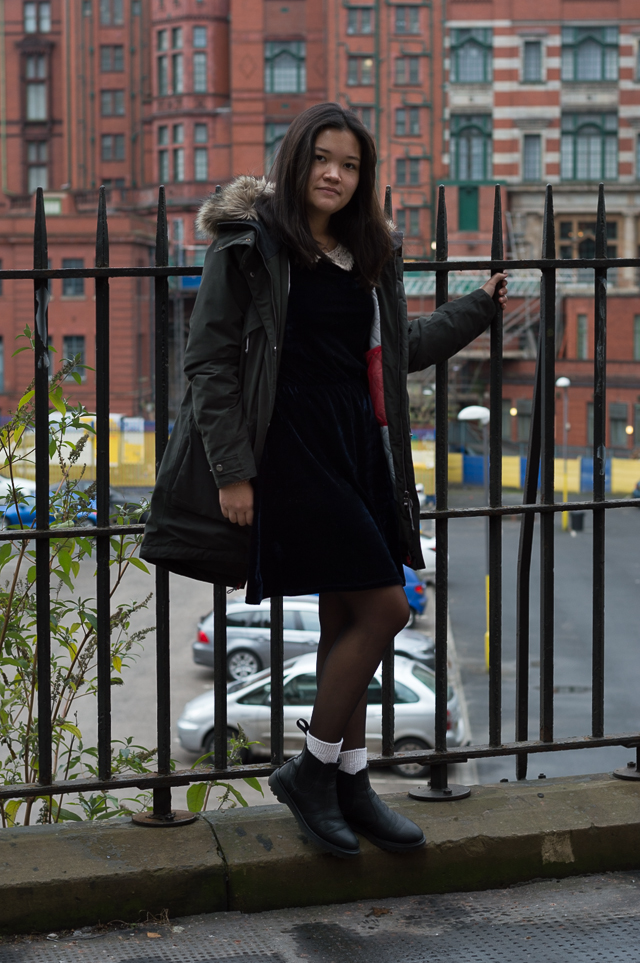 Claire in Manchester, wearing a Didriksons parka, a vintage blue velvet dress and Dr Martens chelsea boots