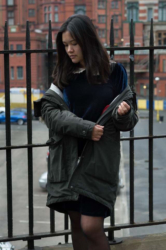 Claire in Manchester, wearing a Didriksons parka and a vintage blue velvet dress