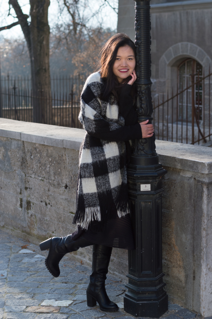 Claire wearing a black sweater and a black midi skirt by & Other Stories, and an oversized scarf by Esprit