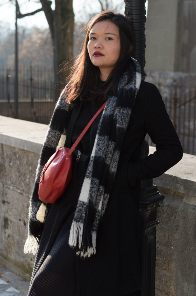 Portrait of Claire wearing a black sweater by & Other Stories, and a black coat and an oversized scarf by Esprit