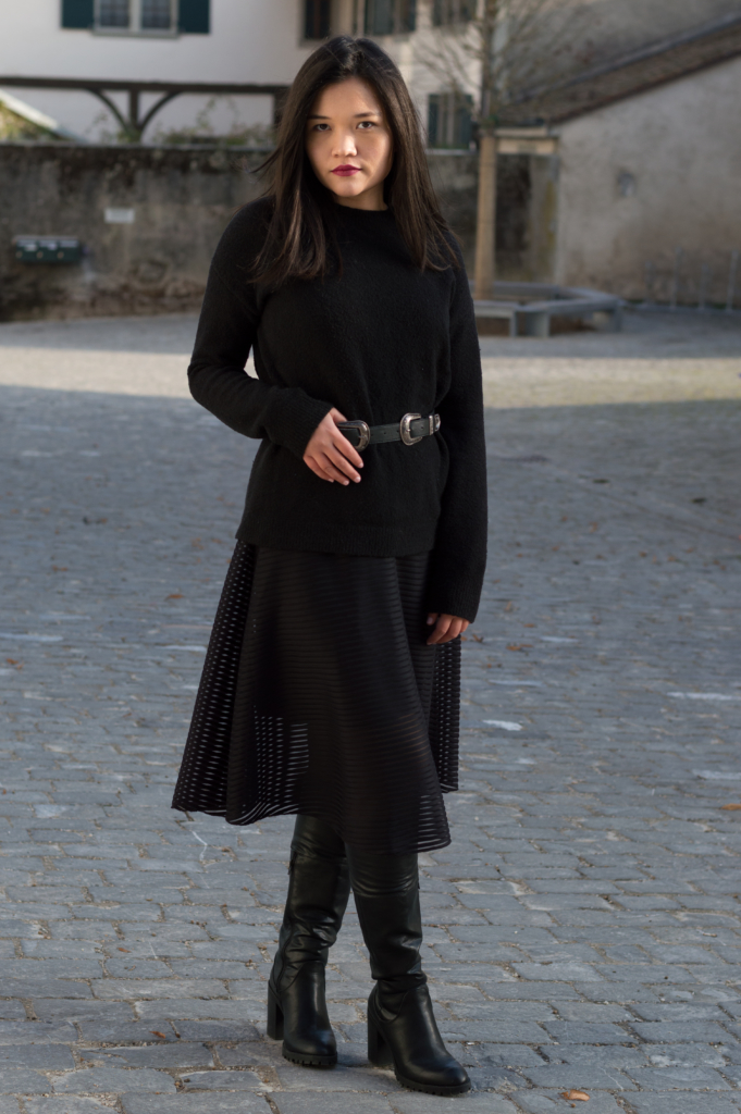 Claire wearing a black sweater and a black midi skirt by & Other Stories