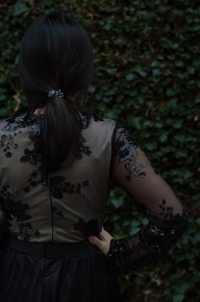 Claire from behind wearing a sequin bodysuit and a pleated skirt