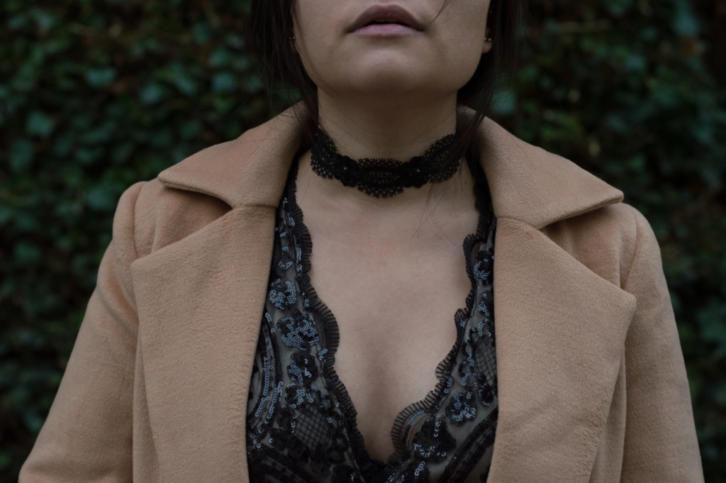Claire wearing a sequin bodysuit, a lace choker and a camel coat