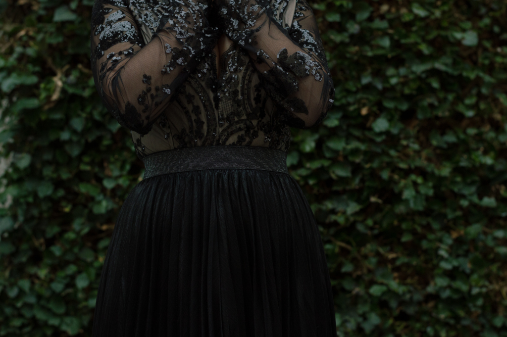 Details: a sequin bodysuit and a pleated skirt