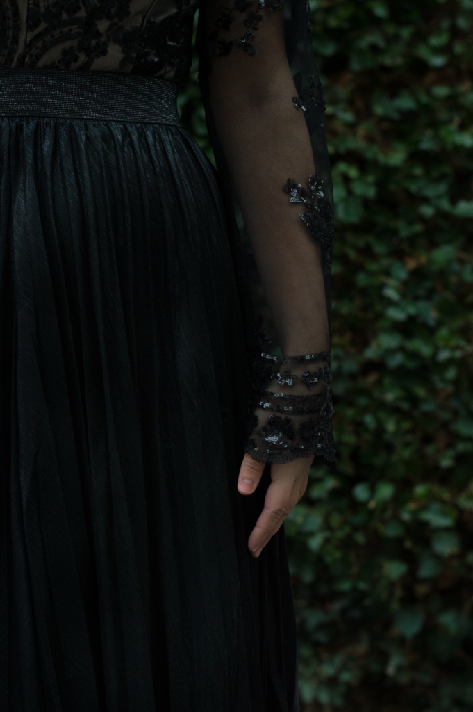Details: sleeve of a sequin bodysuit and a pleated skirt