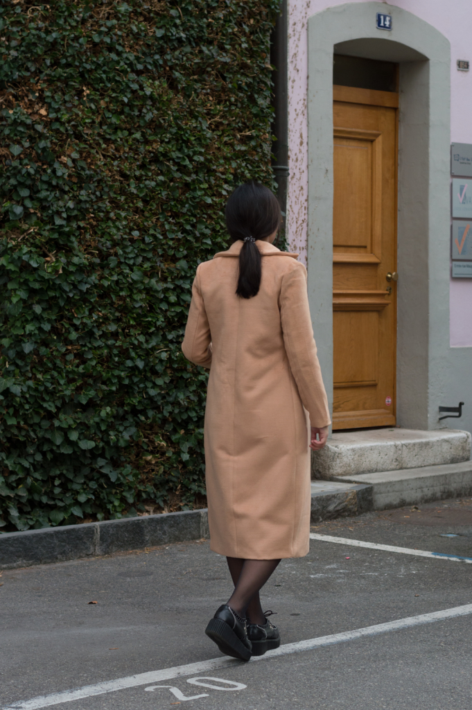 Claire from behind wearing a camel coat
