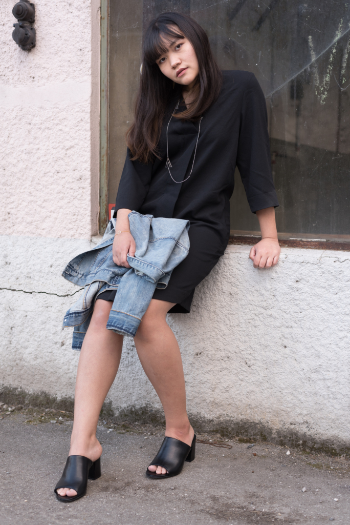 Claire Ketterer wearing a jeans jacket by H&M, a black dress by COS, Dosenbach mules and Shaï jewellery