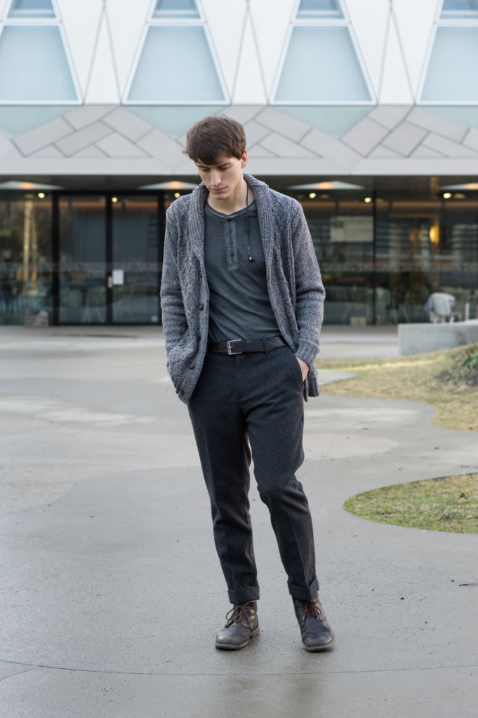 Nicolas wearing wool trousers, a buttoned-collar long-sleeve t-shirt and a knit cardigan
