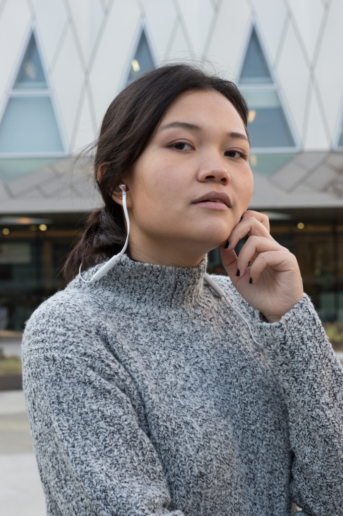 Portrait of Claire wearing the VASA BLÅ earphones by Sudio Sweden