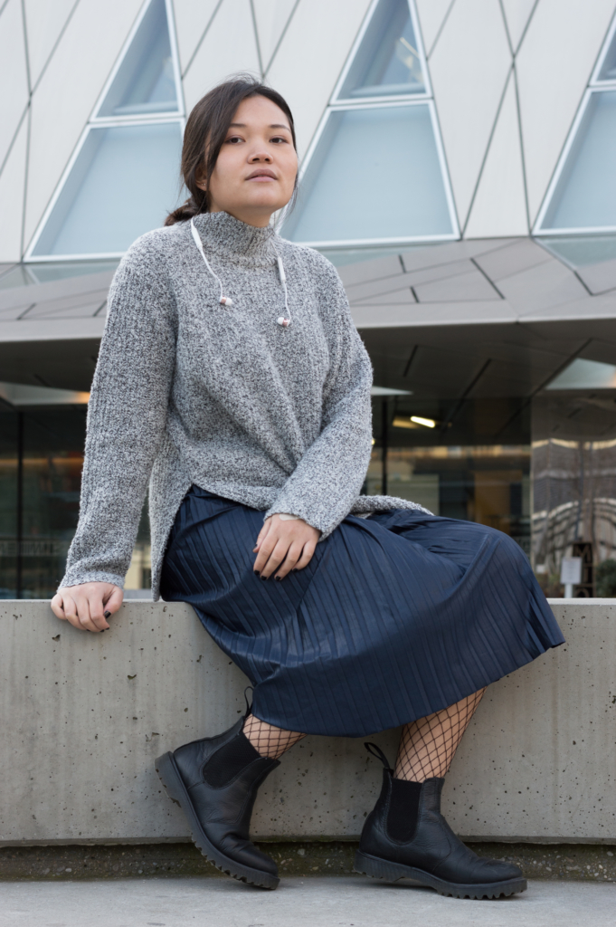 Claire wearing a turtleneck knit sweater, a pleated skirt, fishnet tights and chelsea boots