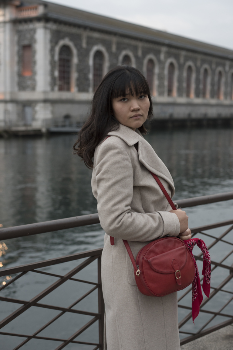 Claire in Geneva, wearing a Caroll coat and a red Longchamp bag