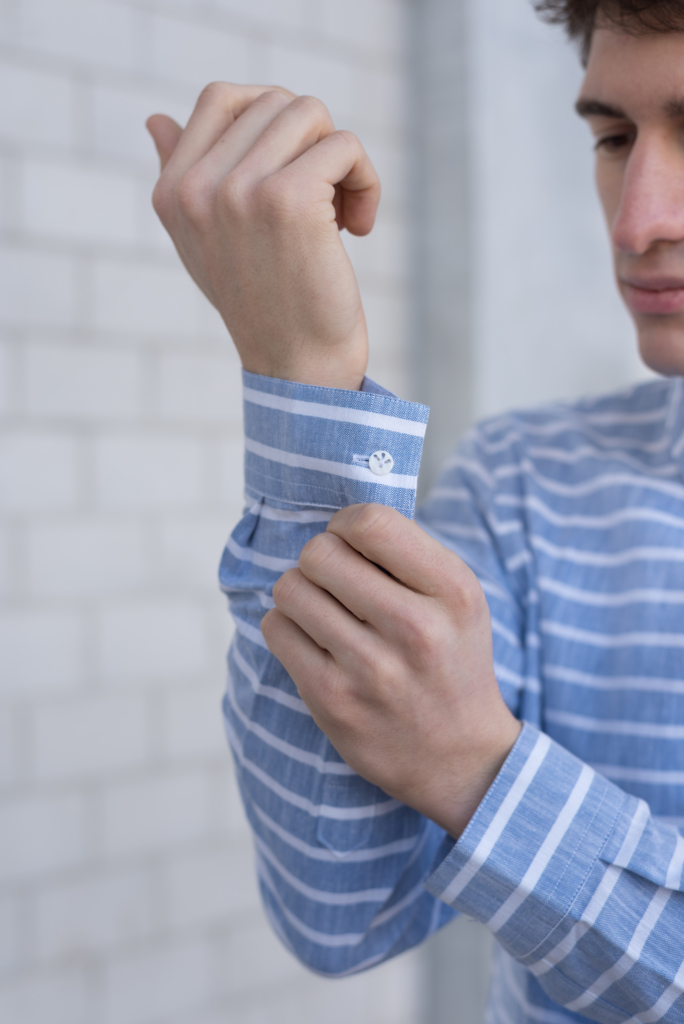 Nicolas buttoning the sleeve of a striped shirt by Solstice