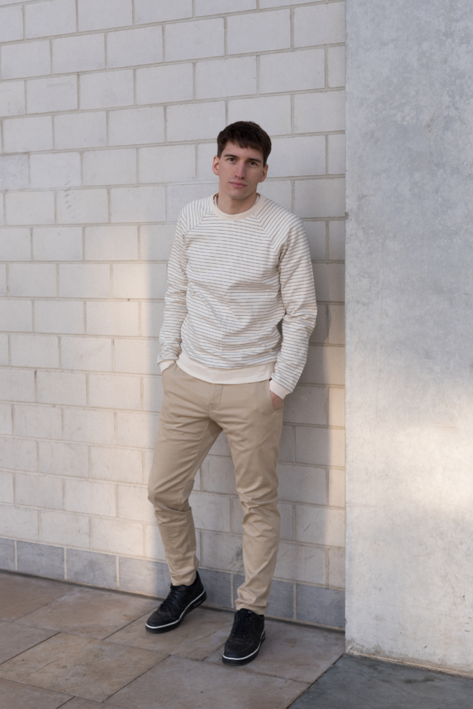 Nicolas wearing a striped sweatshirt and chino pants by Solstice
