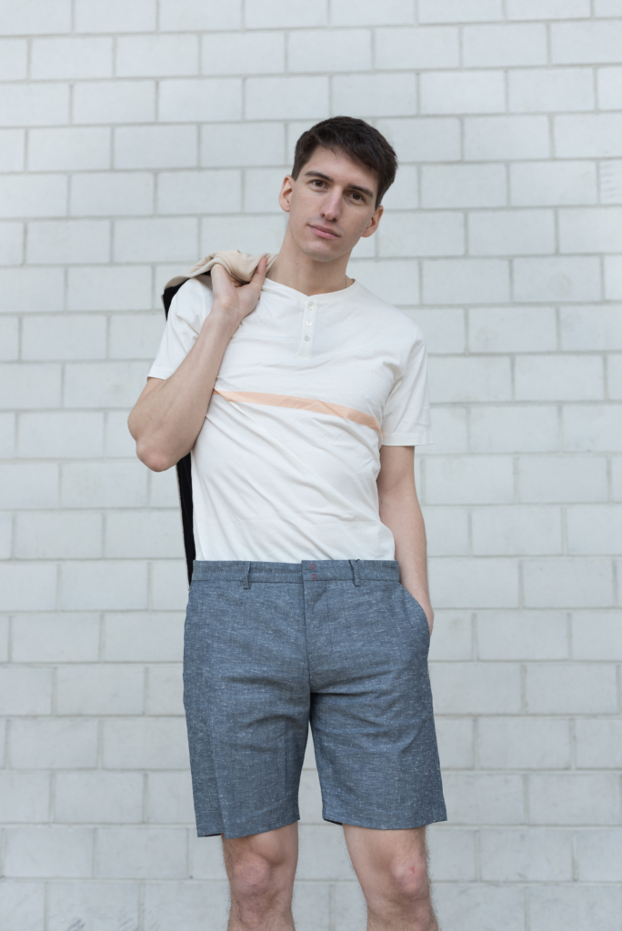 Nicolas wearing a bomber, a buttoned-collar t-shirt with a peach stripe and linen shorts by Solstice