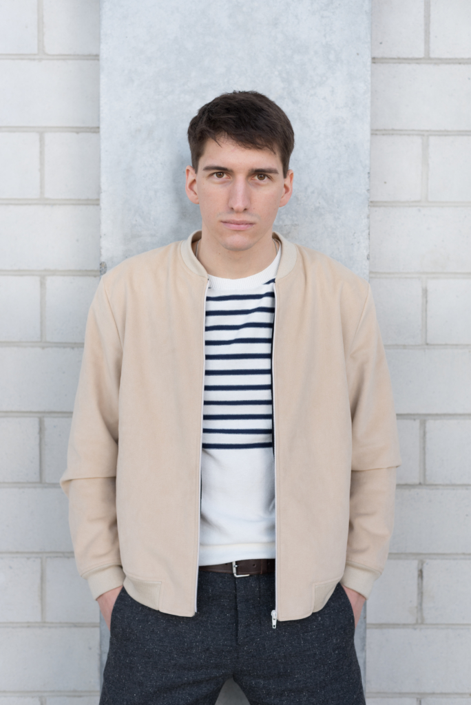 Nicolas wearing a bomber, a reversed jersey sweater and grey woollen pants by Solstice