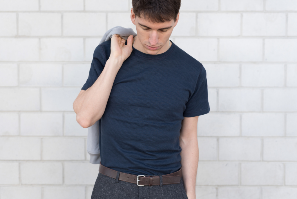 Nicolas wearing a textured navy t-shirt and grey woollen pants by Solstice