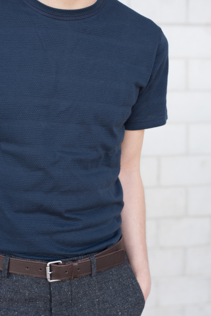 Details: a textured navy t-shirt and grey woollen pants by Solstice
