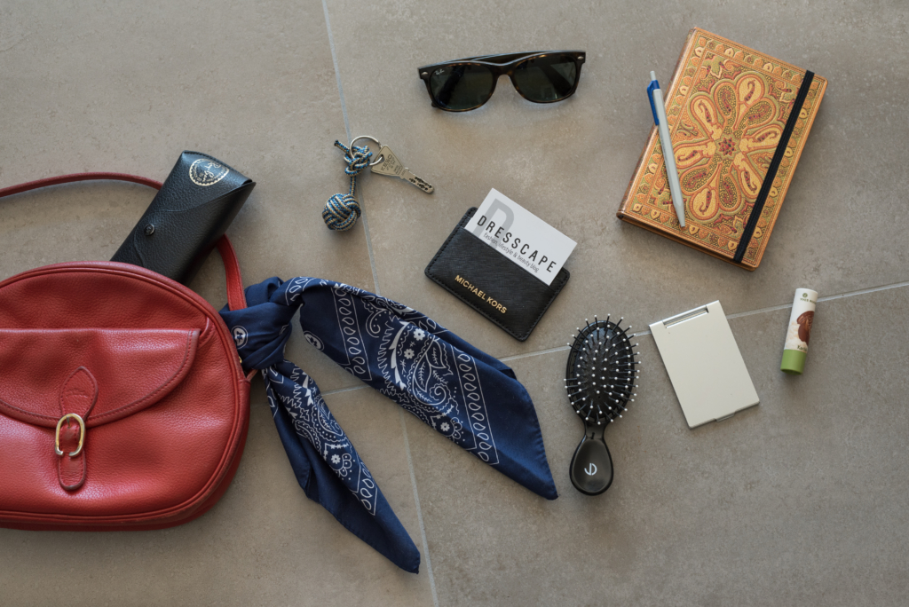 Claire's on-the-go essentials include a Paperblanks notebook, Ray-Ban sunglasses, an Yves Rocher lip balm, a Michael Kors cardholder in a vintage Longchamp crossbody bag