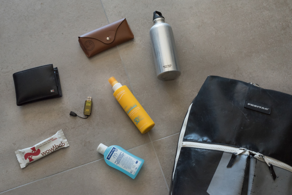 Nicolas' on-the-go essentials include Ray-Ban sunglasses, a Sigg bottle, a Tommy Hilfiger wallet, a healthy snack by Wow!bab, an USB key, and a hand sanitizer in a Freitag backpack