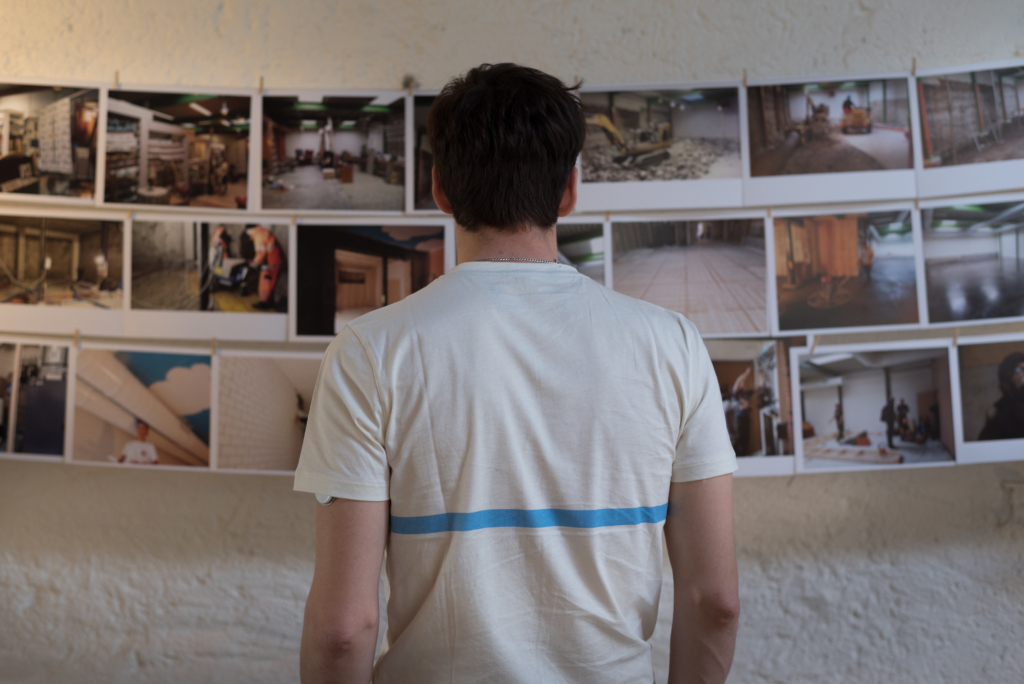 Nicolas looking at the pictures of the premises' renovation process