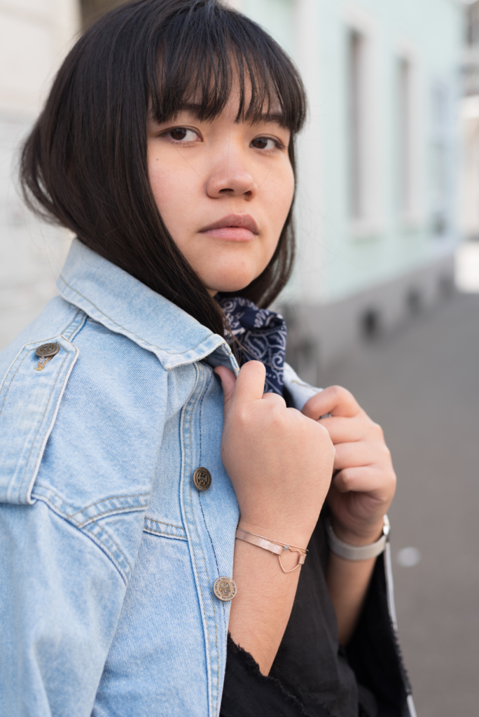 Portrait of Claire wearing a vintage jeans jacket and a blue bandana, as well as TodayDesigner and Lylan jewellery and a Calvin Klein watch