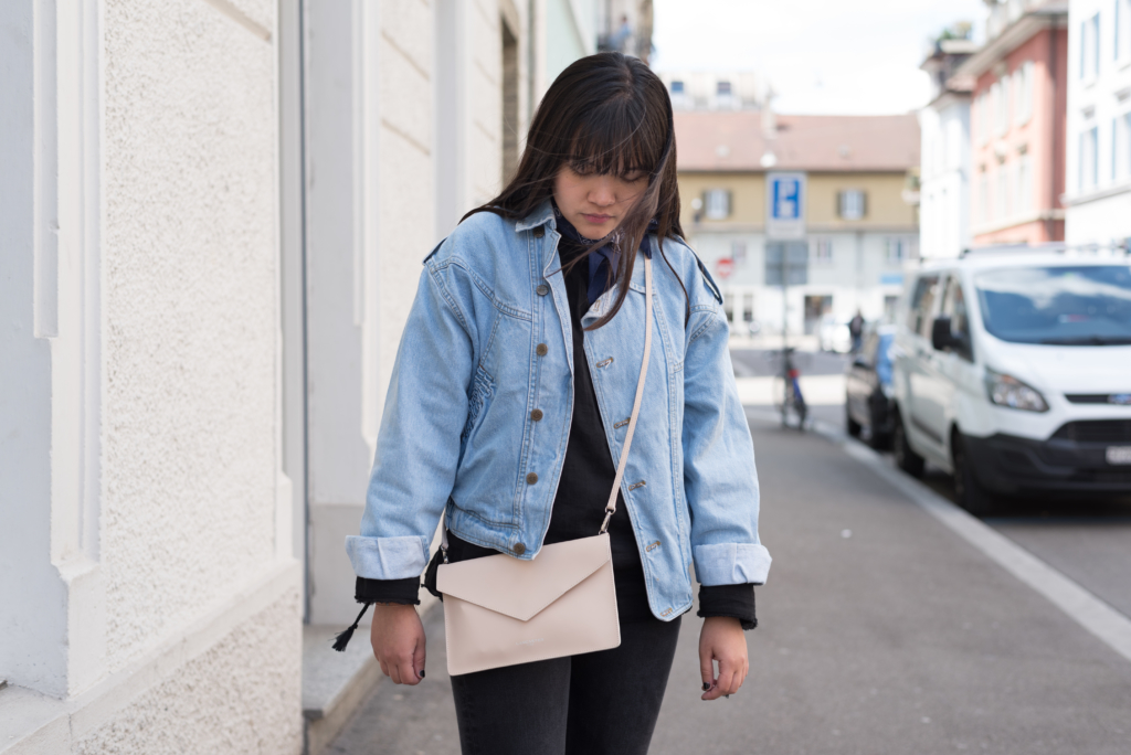 Portrait of Claire wearing a vintage jeans jacket, a blue bandana, a And Other Stories top and a Lancaster clutch