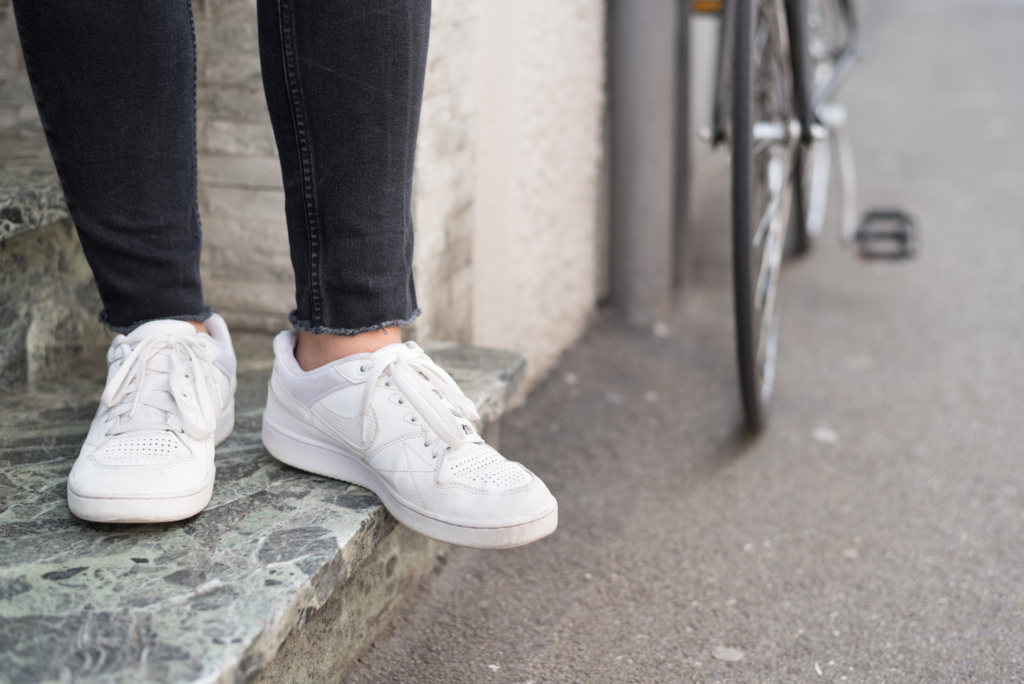 Details: H&M ripped black jeans and Nike white sneakers