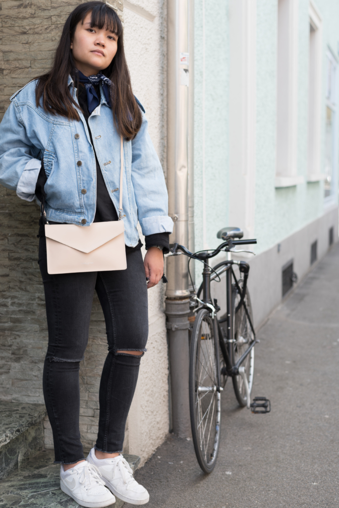 Portrait of Claire wearing a vintage jeans jacket, a blue bandana, a And Other Stories top, H&M ripped black jeans, Nike sneakers and a Lancaster clutch