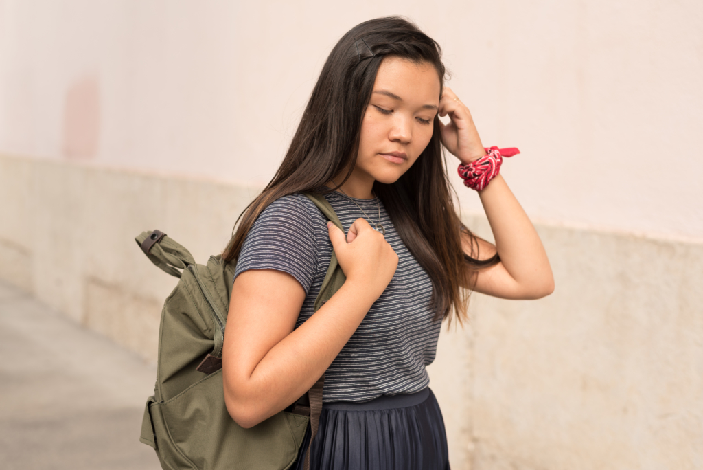 Portrait of Claire wearing a t-shirt by A.P.C, a navy pleated skirt by Topshop and a khaki backpack