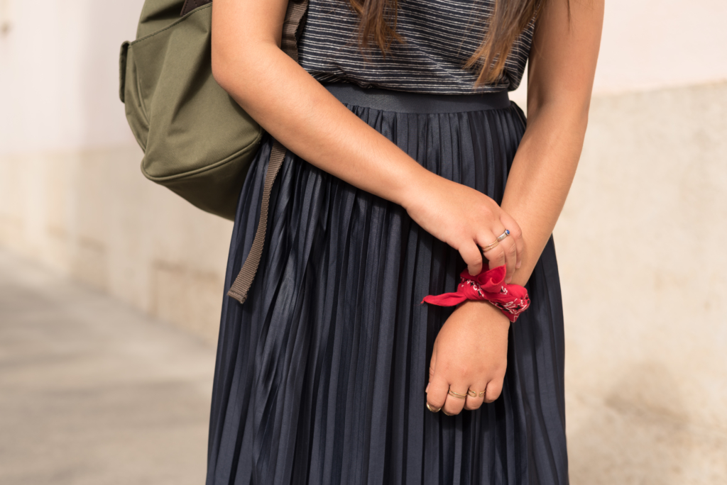 Claire wearing a t-shirt by A.P.C, a navy pleated skirt by Topshop, a red bandana as a bracelet and a khaki backpack