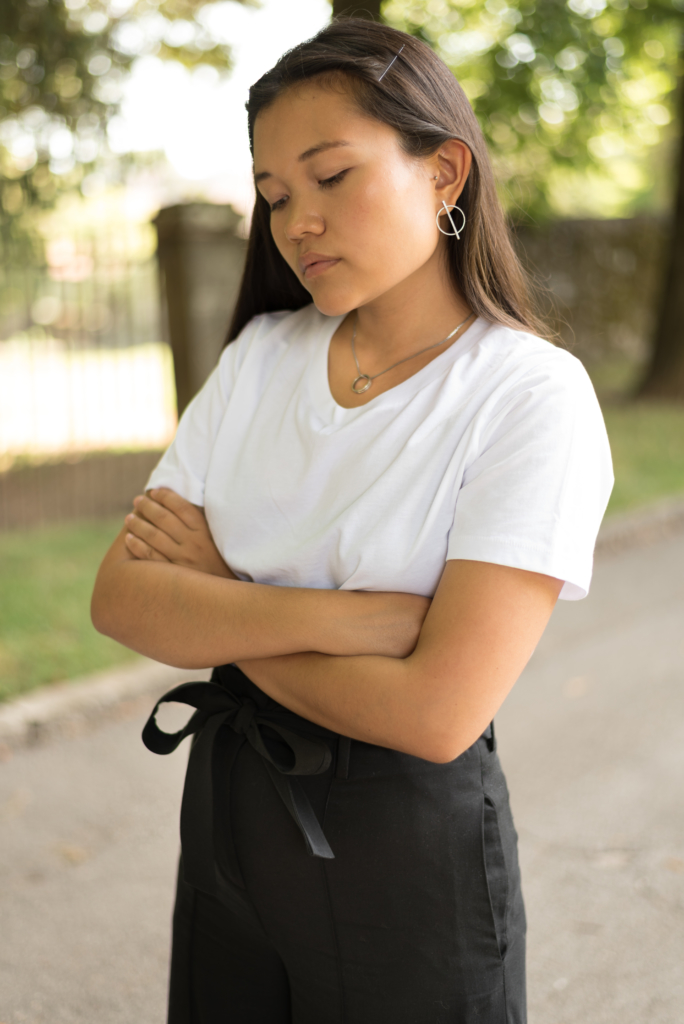 Claire wearing a COS white oversize t-shirt, COS black trousers and Happiness Boutique geometric earrings