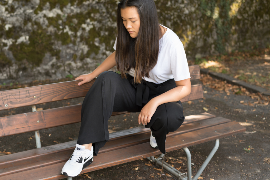 Claire wearing a COS white oversize t-shirt, COS black trousers and Nike sneakers