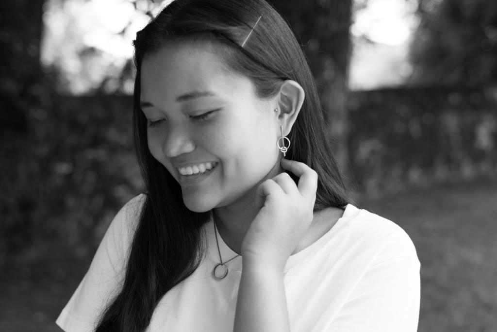 Portrait of Claire wearing a COS white oversize t-shirt and Happiness Boutique geometric earrings