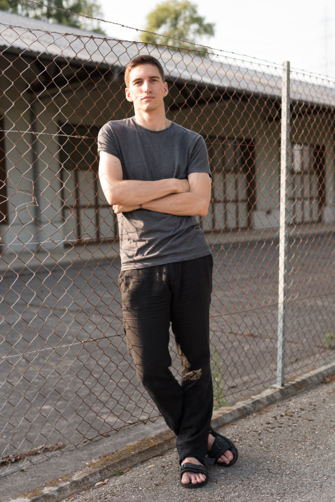 Nicolas wearing a dark grey T-Shirt and black linen trousers.