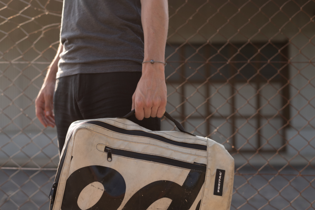 Nicolas wearing a dark grey T-Shirt, black linen trousers and a cream white Freitag bag.