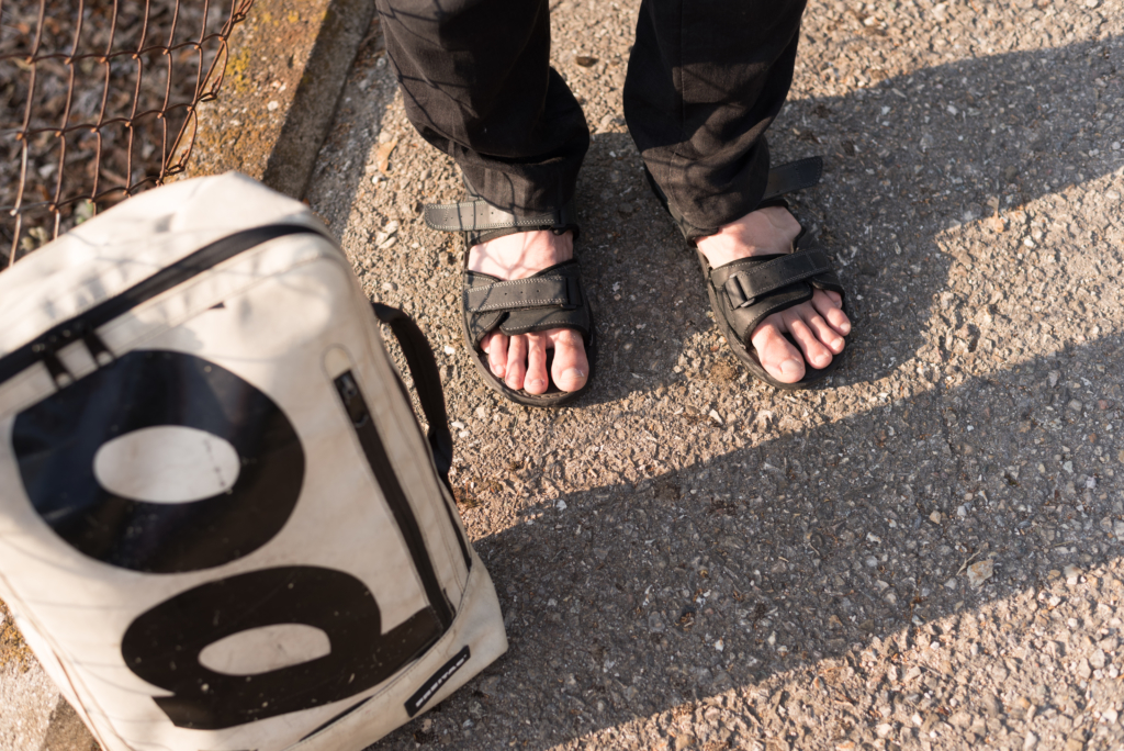 Nicolas wearing black sandals, black linen trousers and a cream white Freitag bag.