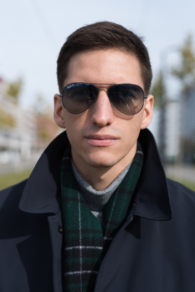 Nicolas Moser interpreting the aviator look whith a chic coat and Ray-Ban sunglasses.