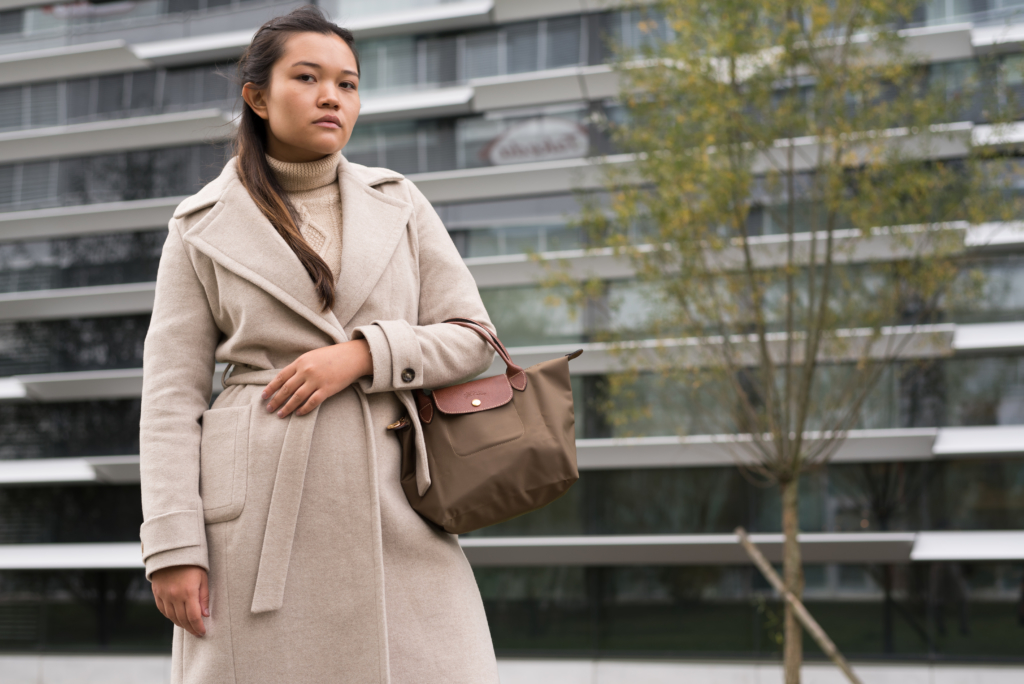 Claire Ketterer with a beige coat by Caroll and a Longchamp handbag