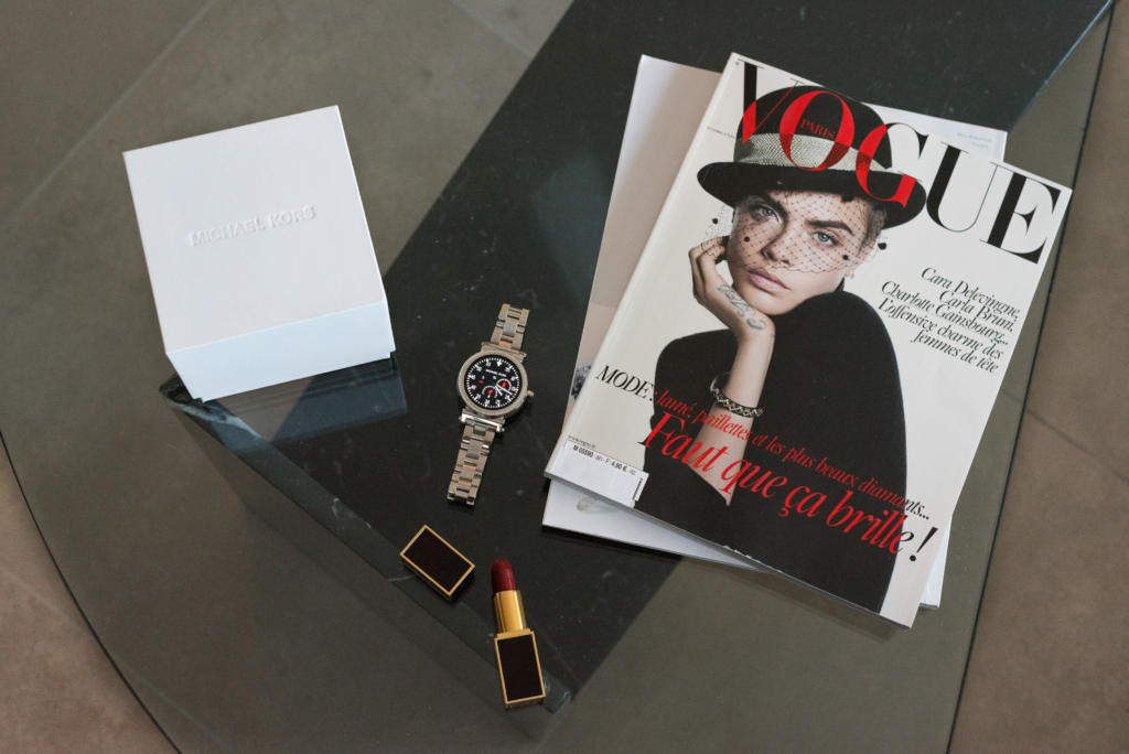 Details: a smartwatch by Michael Kors with its rangement box, a lipstick and a Vogue magazine