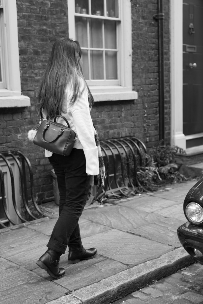 Black and white picture of Claire, casually walking in London