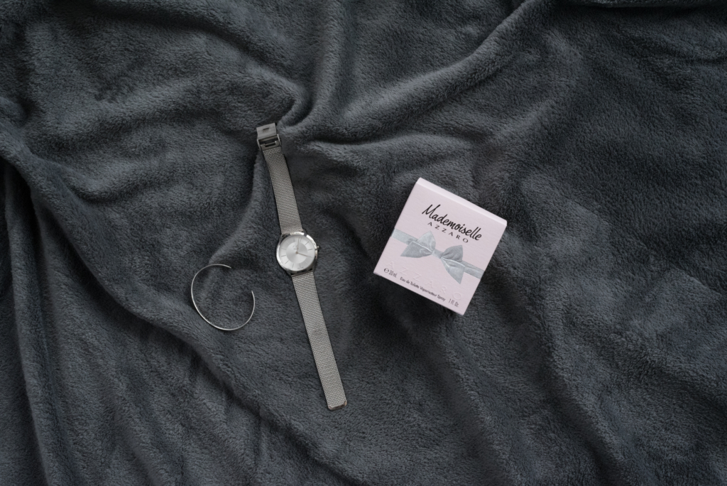 Flatlay of a Calvin Klein watch, a Thomas Sabo bracelet and Mademoiselle Azzaro fragrance