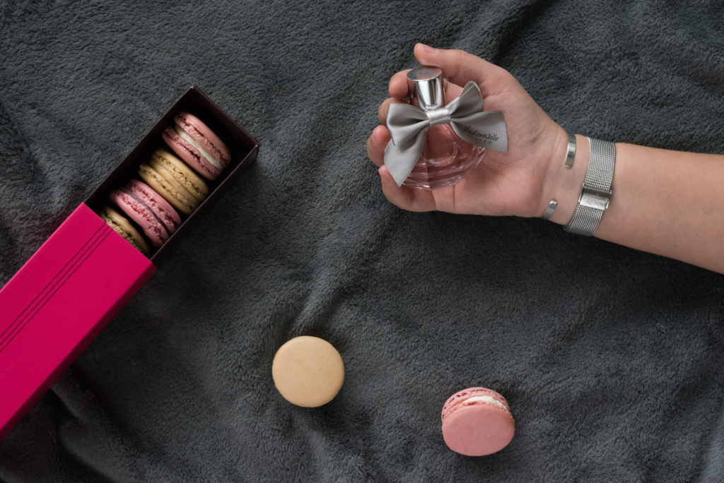 Flatlay of the Mademoiselle Azzaro fragrance along with macarons