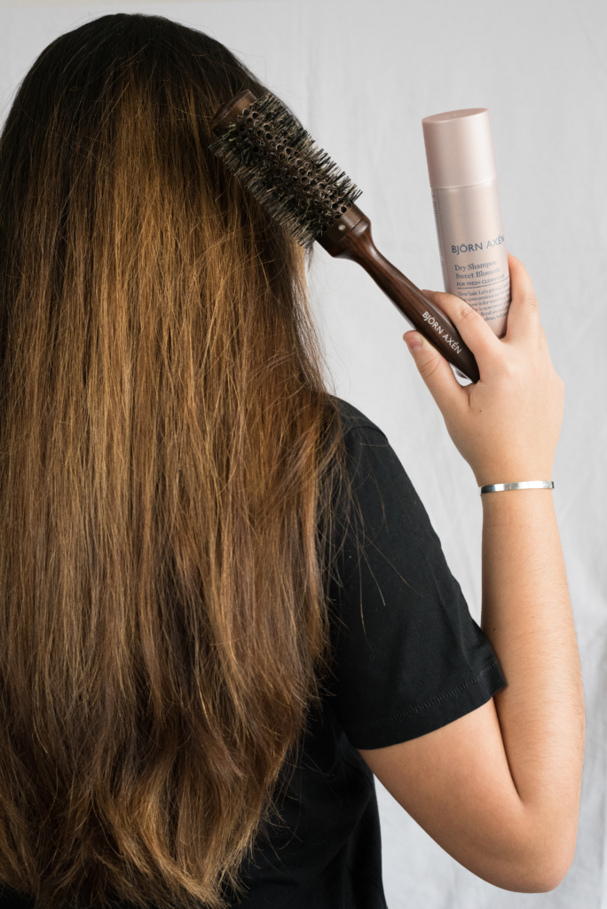 Claire holding a dry shampoo and hair brush by Björn Axén