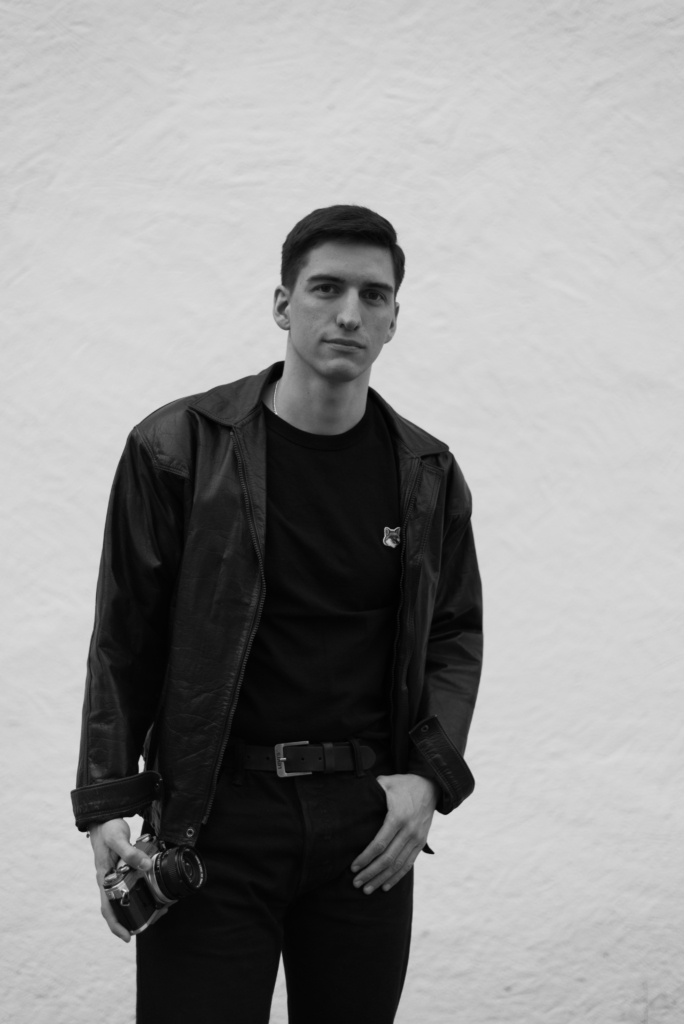 Black and white pic of all black look featuring Nicolas Moser holding an analogue camera