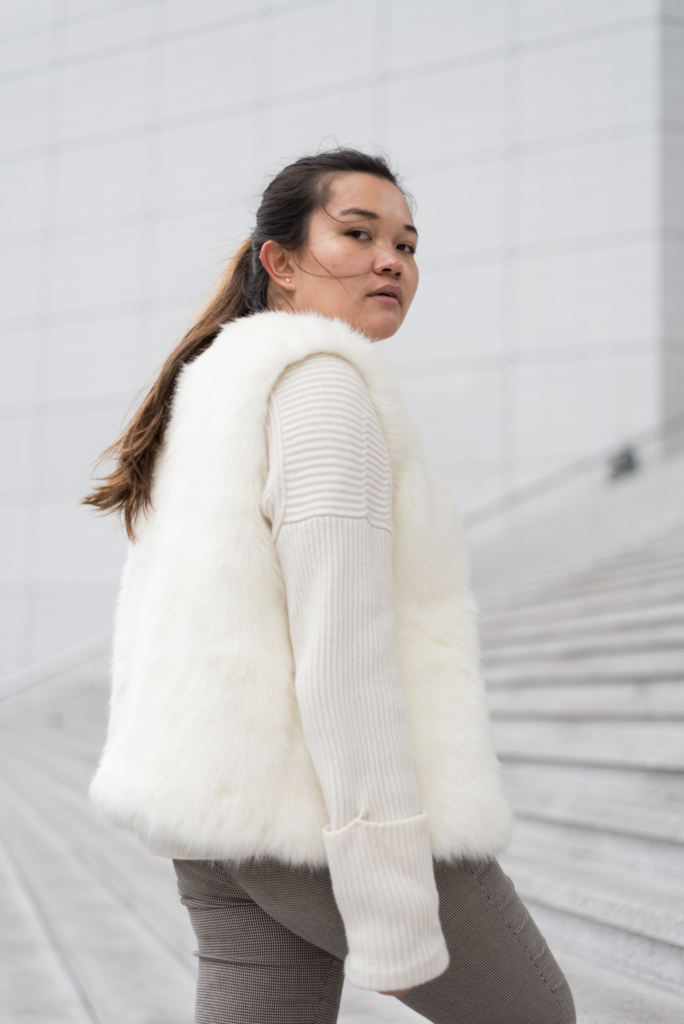 Claire in Paris wearing a faux fur vest over a white knit sweater
