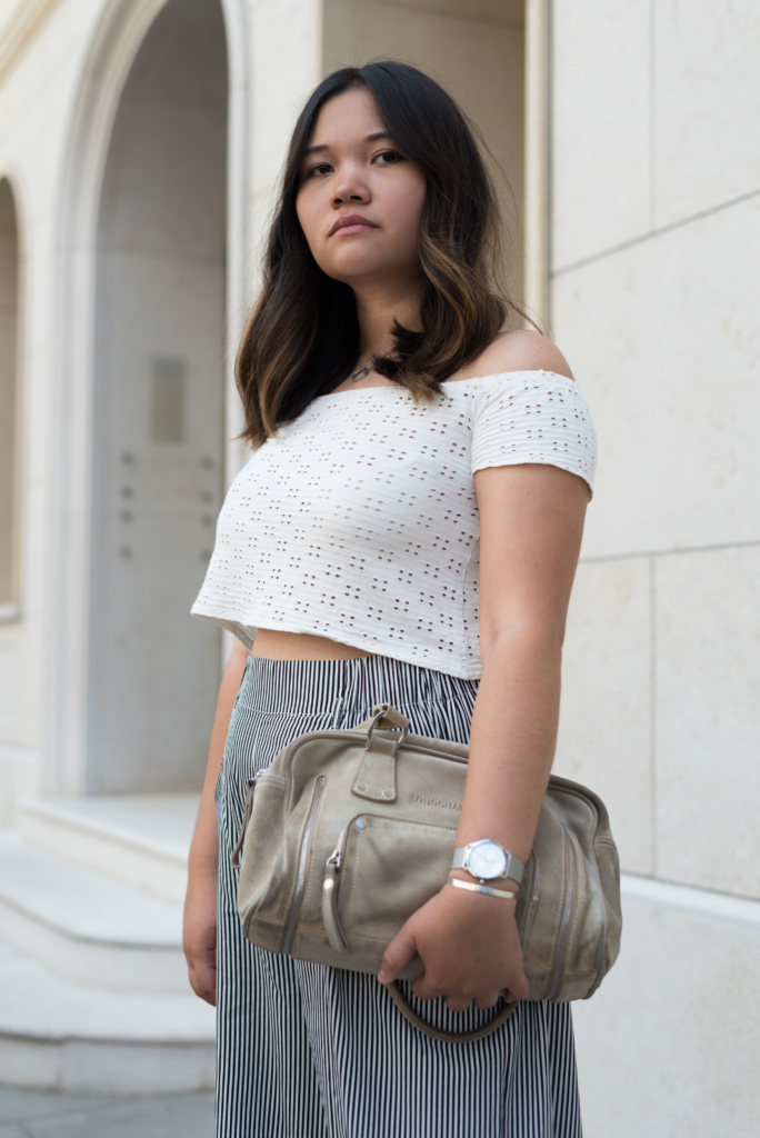 Claire Ketterer wearing a white crop top, black and white wide-leg pants and her Longchamp bag