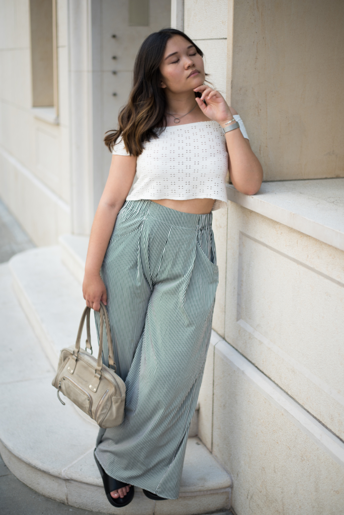Claire Ketterer wearing a white crop top, black and white wide-leg pants, black slides and her Longchamp bag