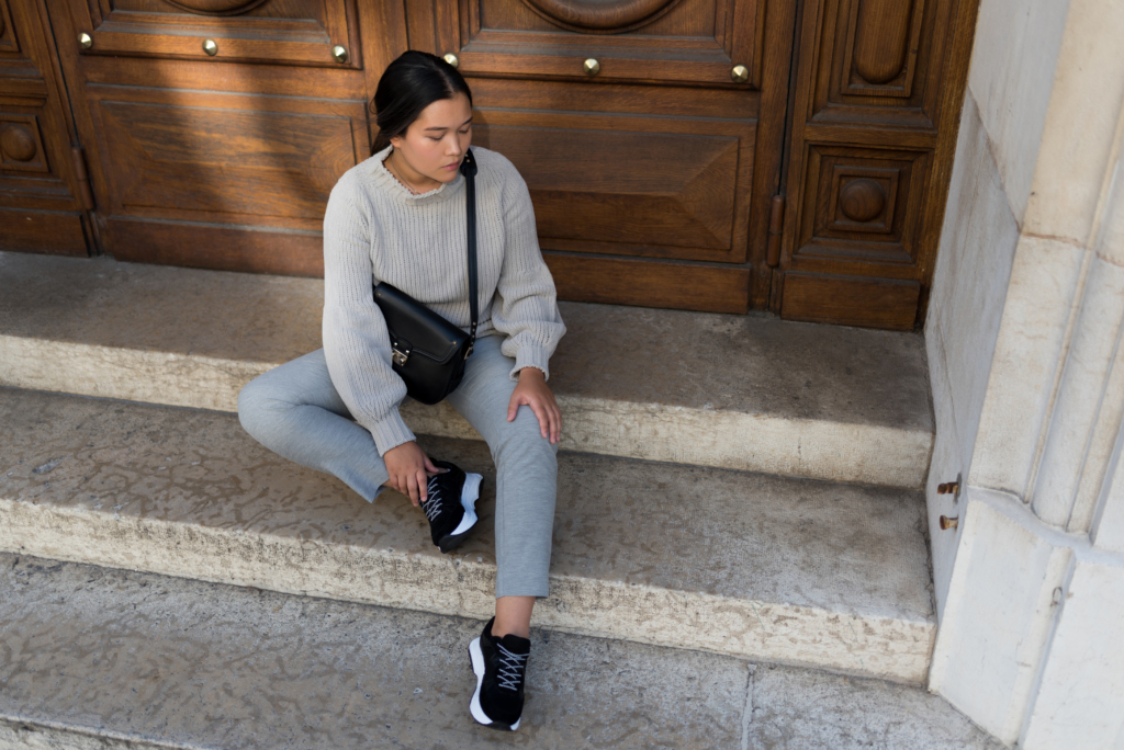 Claire Ketterer sitting on stairs, wearing an all grey Stefanel outfit