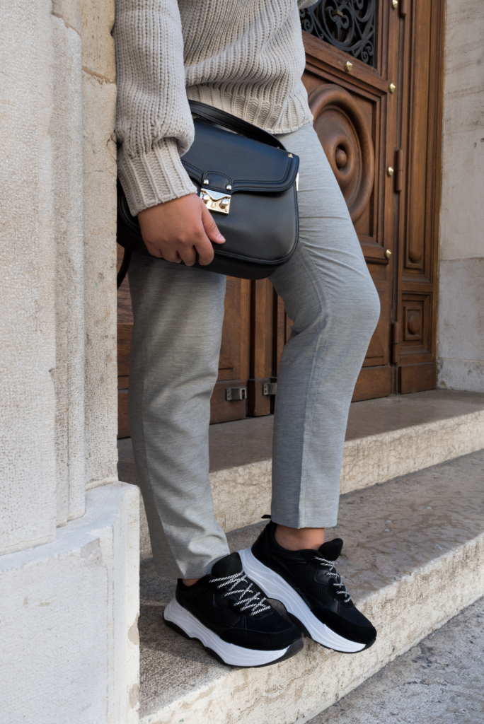 Claire Ketterer showing of her minimal style: all grey Stefanel outfit, black bag and black and white shoes